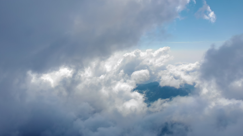 Flying through beautiful thick fluffy clouds. Amazing timelapse of soft white clouds moving slowly on the clear blue sky in pure daylight. Direct view from the cockpit. Royalty-Free Stock Footage #1036992296