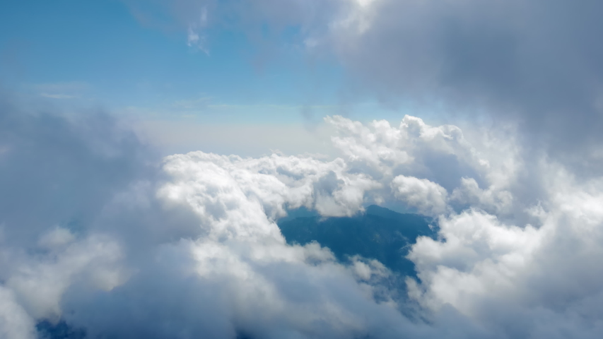 Flying through amazingly beautiful cloudscape. Picturesque timelapse of white fluffy clouds moving softly on the clear blue sky in pure sunshine. Direct view from the cockpit. Royalty-Free Stock Footage #1036992314