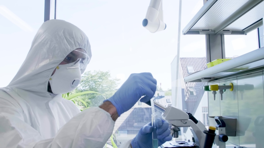 Scientists in protection suits and masks working in research lab using laboratory equipment: microscopes, test tubes. Biological hazard, pharmaceutical discovery, bacteriology and virology. Royalty-Free Stock Footage #1037004764