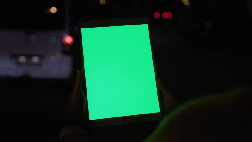 Young woman using modern tablet gadget with greenscreen mock-up technology while standing on busy traffic road at night. | Shutterstock HD Video #1037007668