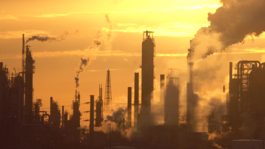 oil refinery factory high towers emitting smoke at sunset