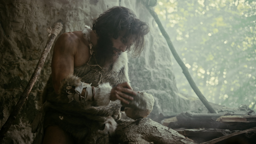 Primeval Caveman Wearing Animal Skin Hits Rock with Sharp Stone and Makes Primitive Tool for Hunting Animal Prey. Neanderthal Using Hand axe to Create first Millstone. Slow Motion Shot Royalty-Free Stock Footage #1037017256