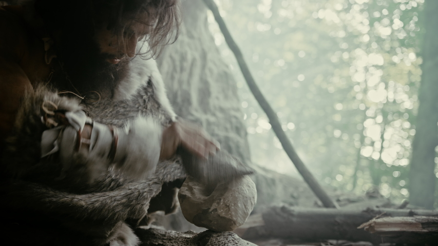 Primeval Caveman Wearing Animal Skin Hits Rock with Sharp Stone and Makes Primitive Tool for Hunting Animal Prey. Neanderthal Using Hand axe to Create first Wheel. Slow Motion Shot Royalty-Free Stock Footage #1037017259
