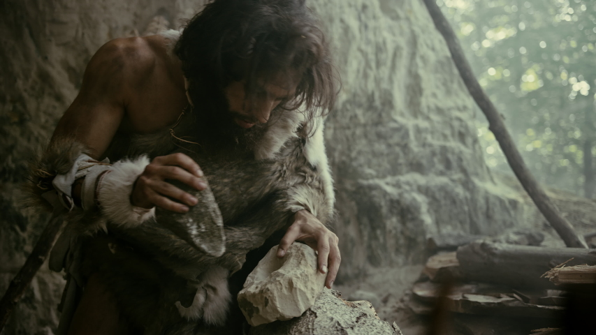 Primeval Caveman Wearing Animal Skin Hits Rock with Sharp Stone and Makes First Primitive Tool for Hunting Animal Prey. Neanderthal Using Flint Rock. Dawn of Human Civilization. Slow Motion Closeup