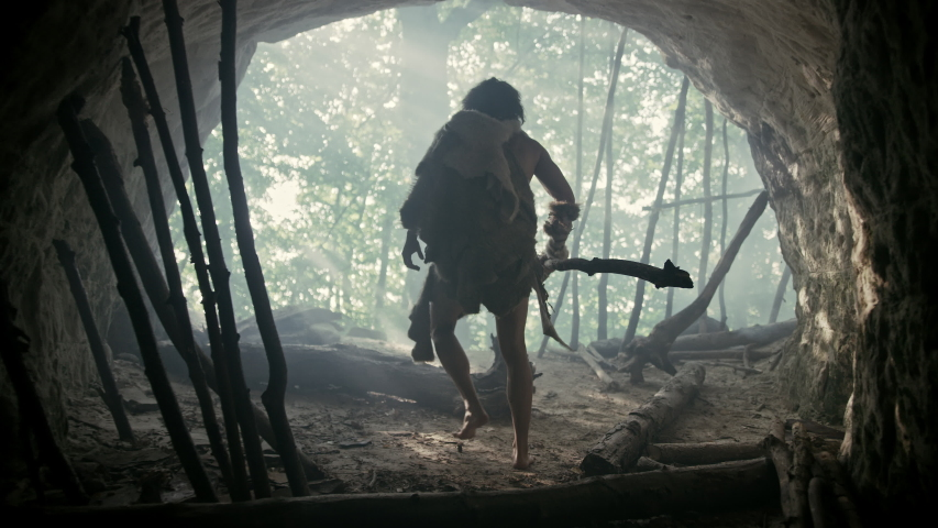 Primeval Caveman Wearing Animal Skin and Fur Holds Stone Tipped Spear Comes out of His Cave into Prehistoric Forest Ready to Hunt. Neanderthal Going Hunting into the Jungle.Following and Portrait Shot