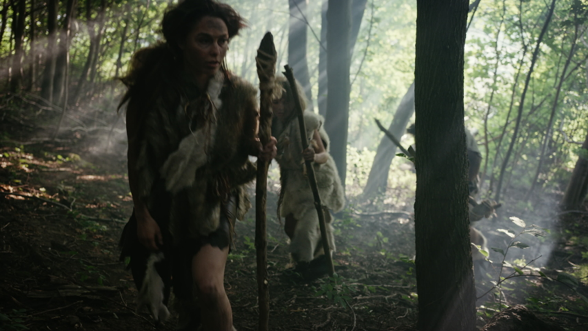 Tribe of Hunter-Gatherers Wearing Animal Skin Holding Stone Tipped Tools, Explore Prehistoric Forest in a Hunt for Animal Prey. Neanderthal Family Hunting in the Jungle or Migrating. Side Arc View Royalty-Free Stock Footage #1037017616