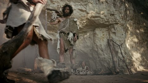 Tribe Leader Wearing Animal Skin Stands at Cave Entrance Looks Around. Family Clan Members Preparing Food, Building Bonfire, Handle Hides, Working, Hunting. Neanderthals Way of Life