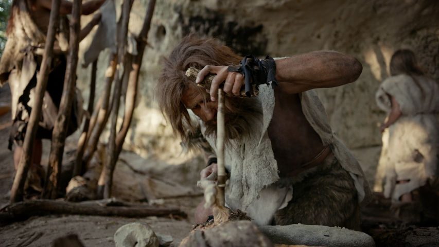Primeval Caveman Wearing Animal Skin Trying to make a Fire with Bow Drill Method. Kindle First Man-Made fire in the Human Civilization History. Making Fire for Cooking. Slow Motion