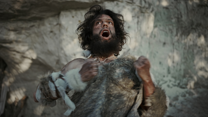 Portrait of Primeval Caveman Wearing Animal Skin Does Threatening Chest Beating and Screaming, Defending His Cave and Territory in the Prehistoric Times. Prehistoric Neanderthal or Homo Sapiens Leader Royalty-Free Stock Footage #1037018204