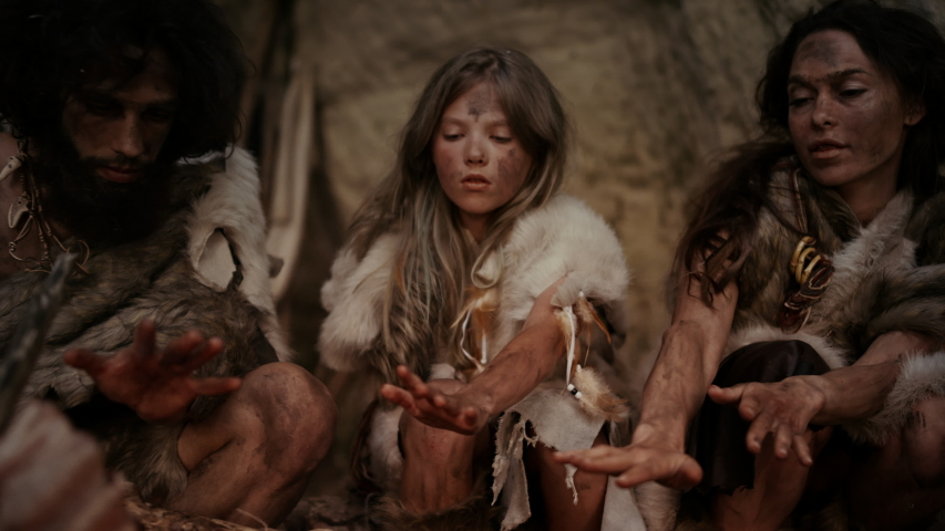 Tribe of Prehistoric Hunter-Gatherers Wearing Animal Skins Live in a Cave at Night. Neanderthal or Homo Sapiens Family Trying to Get Warm at the Bonfire, Holding Hands over Fire, Cooking Food Royalty-Free Stock Footage #1037018339