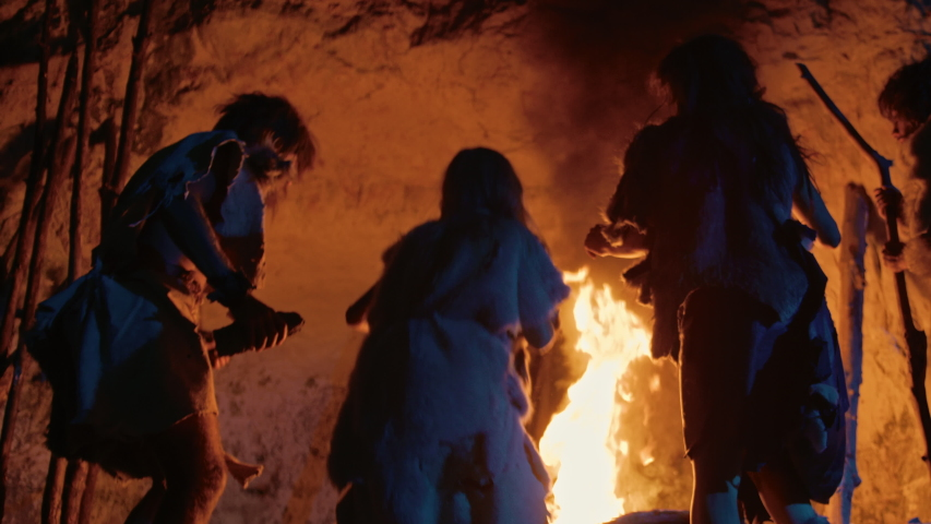 Tribe of Prehistoric Hunter-Gatherers Wearing Animal Skins Dance Around Bonfire Outside of Cave at Night. Neanderthal / Homo Sapiens Family Doing Pagan Religion Dancing Near Fire Back View Slow Motion Royalty-Free Stock Footage #1037018723