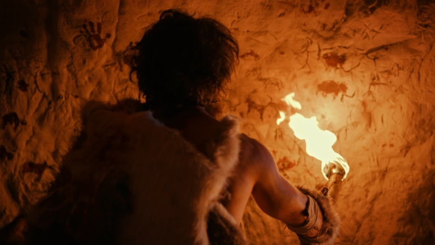 Primeval Caveman Wearing Animal Skin Standing in His Cave At Night, Holding Torch with Fire Looking at Drawings on the Walls at Night. Cave Art with Petroglyphs, Rock Paintings. Back View