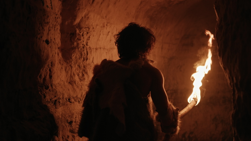 Primeval Caveman Wearing Animal Skin Exploring Cave At Night, Holding Torch with Fire Looking at Drawings on the Walls at Night. Neanderthal Searching Safe Place to Spend the Night.Back View Following
