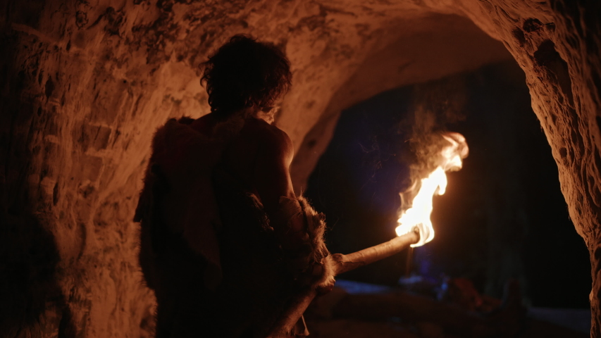 Primeval Caveman Wearing Animal Skin Exploring Cave At Night, Holding Torch with Fire Looking at Drawings on the Walls at Night. Neanderthal Searching Safe Place to Spend the Night.Back View Following | Shutterstock HD Video #1037019491