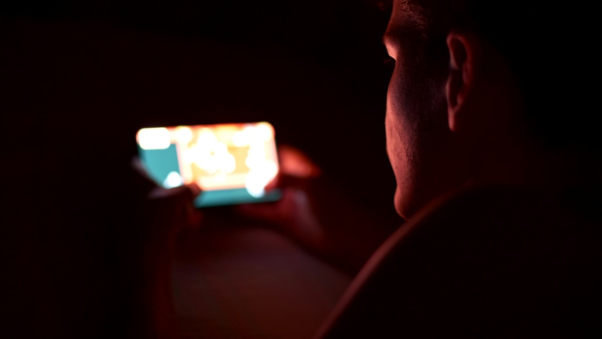 Teenage boy playing a video game on his smartphone in the darkness at night. UHD