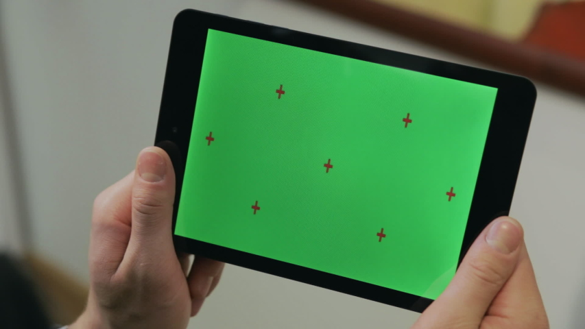 Man holding in hands tablet pc with chroma key screen. Man using tablet with green screen for internet surfing online. Close up chromakey screen with marker