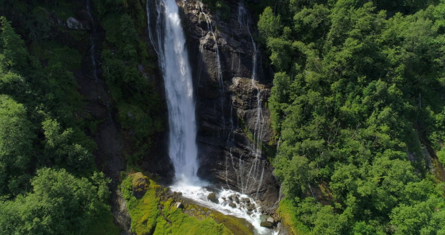 Aerial: Drone shot of beautiful waterfall on cliff amidst trees in forest - Geiranger Fjord, Norway | Shutterstock HD Video #1037051888