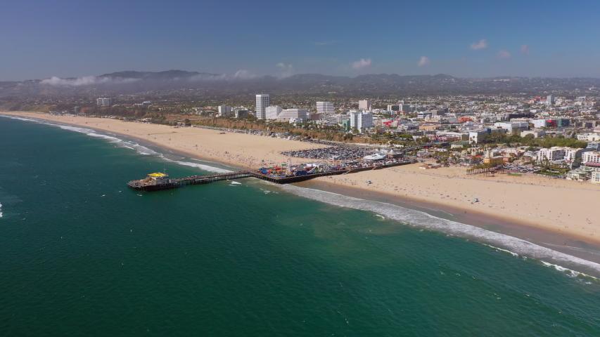 Aerial: Santa Monica Cityscape with Pier, Beach and Mountain Range in the Background - Santa Monica, California