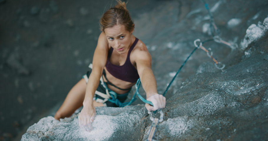 Young fit woman lead rock climbing outdoors, climber clipping into quick draw, cinematic slow motion rock climbing moment