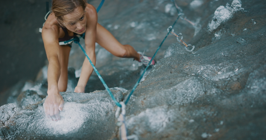 Young fit woman rock climbing outdoors, rock climber reaching for hold and falling, slow motion