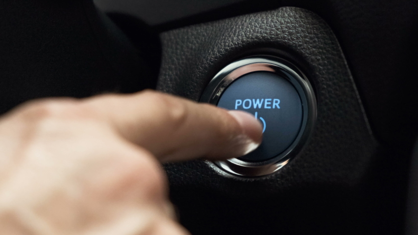 Pushing blue  power ignition button to start keyless ignition hybrid car engine