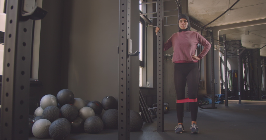 Closeup portrait of young attractive athletic muslim female in hijab doing leg resistance training in gym indoors   Shutterstock HD Video #1037069138