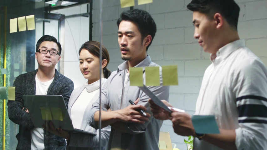 Young asian business man presenting idea to teammates by drawing a diagram on meeting room glass wall | Shutterstock HD Video #1037075399
