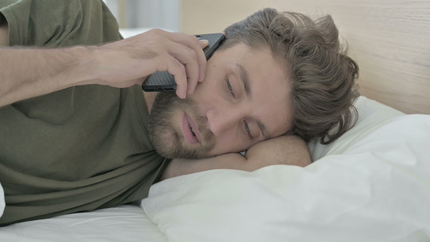 Close-up of Young Man talking on Cellphone in Bed | Shutterstock HD Video #1037085977