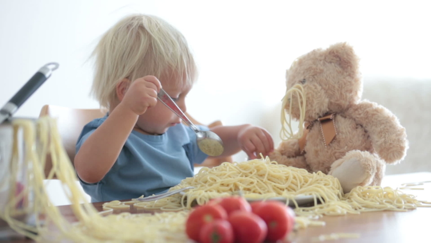 Little baby boy, toddler child, eating spaghetti for lunch and making a mess at home, pot with spaghetti and tomatoes on the table | Shutterstock HD Video #1037090816