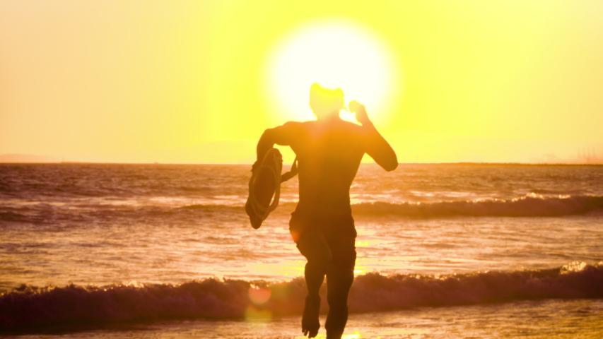 Male lifeguard running along the beach #1037096948