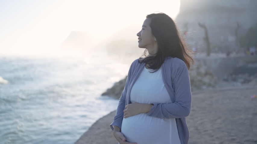 Pregnant mother stands next to a cliff against a mountain and sea background   Shutterstock HD Video #1037116091