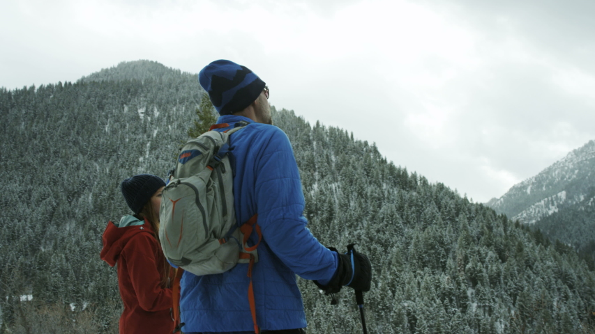Man and woman enjoy the view in snow covered mountains  | Shutterstock HD Video #1037118239