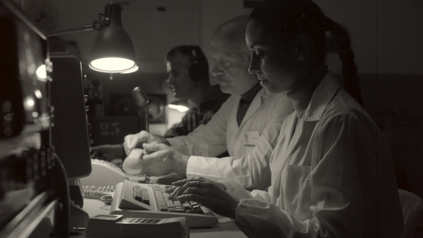 Vintage sci-fi scientists working in a operation room: they are sitting at desk, answering phone calls, using computers and making radio transmissions