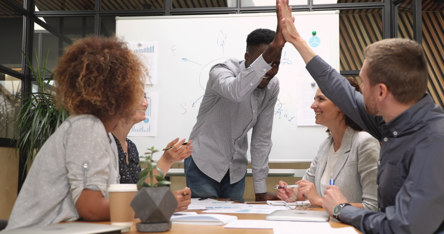 Happy diverse businessmen designers give high five during team corporate brainstorm, african group leader and caucasian partner coworker celebrate good successful teamwork result at company briefing | Shutterstock HD Video #1037121257