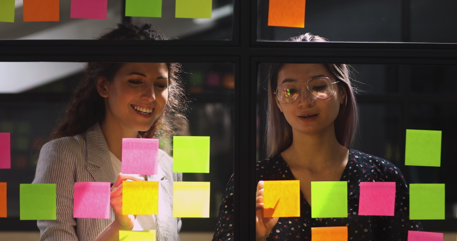 Happy friendly diverse female colleagues talking working with sticky notes, smiling professional team two businesswomen sharing creative ideas replacing stickers planning project write on glass wall