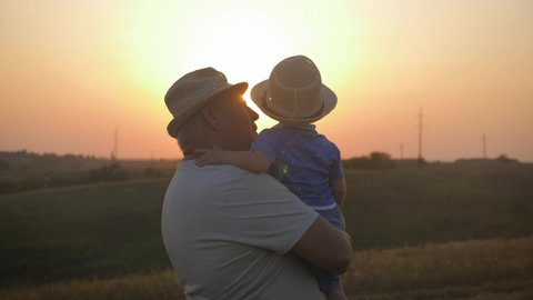 Two generations silhouette of a mature grandfather and little grandson play at sunset.