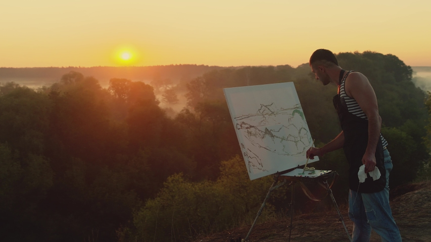 Landscape painter. The view from the back of man painting a natural scenery with oil paints   Shutterstock HD Video #1037130200