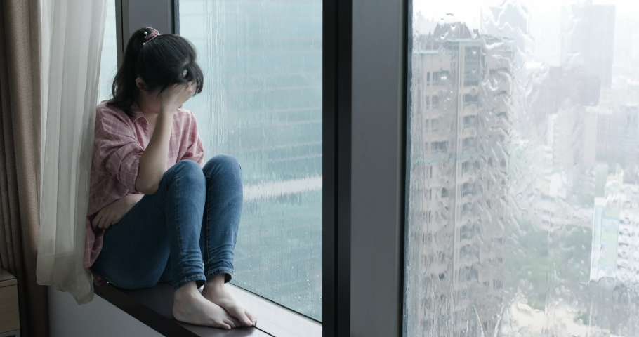 asian woman cry and sit by window on a rainy day #1037136095