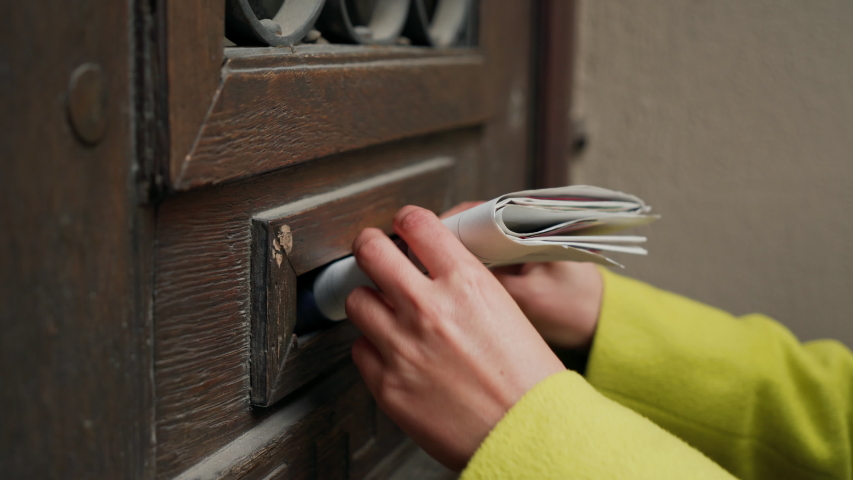 Postman puts a letter or newspaper or magazine in the mailbox at the door of a residential building or a person puts a brochure with advertising. Close-up   Shutterstock HD Video #1037142755