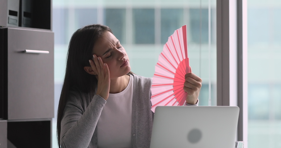 Tired sweaty young woman holding waving fan suffer complain on heat in office, overheated annoyed employee sweating feel uncomfortable hot in summer weather problem no air conditioner at workplace