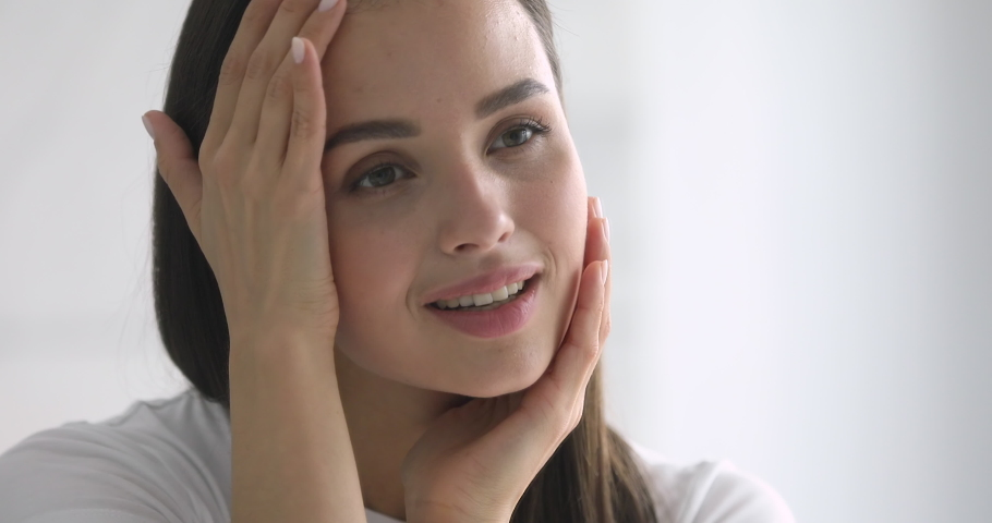 Happy attractive young woman touching pretty face after applying cream do make up looking in mirror enjoy natural beauty and healthy clean soft moisturized hydrated skin care treatment, close up view