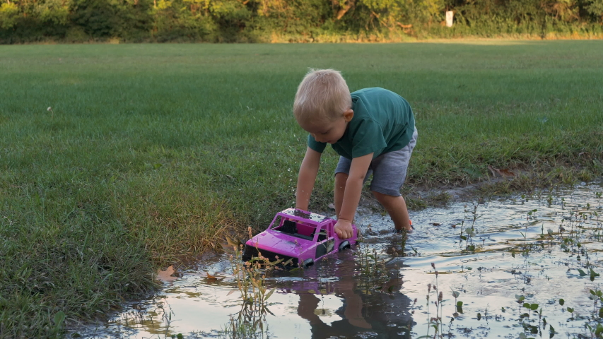 Child (boy, toddler) playing with a pink toy truck in a mud after rain on a flooded playground. Summertime, sunny day, outdoor activity   | Shutterstock HD Video #1037148821