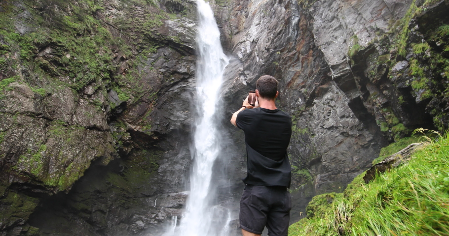 Traveler shooting a waterfall in the Swiss alps with his cellphone. | Shutterstock HD Video #1037157332