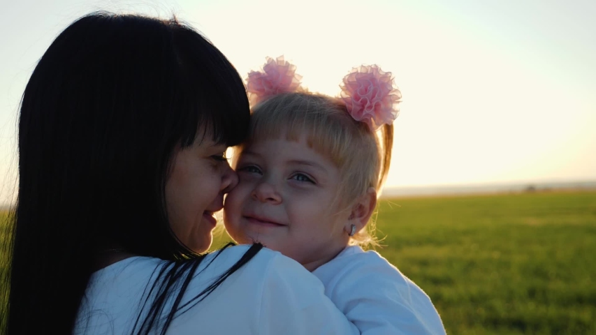 A happy family. Young mother hugs little daughter in a field in the sun at sunset. Tenderness of family relationships. Concept of family love. | Shutterstock HD Video #1037163401