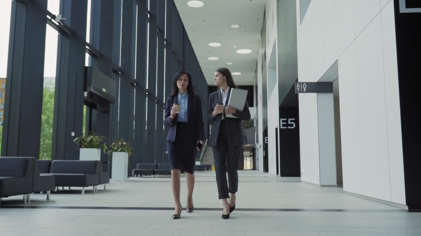 Full length shot of two businesswomen, young professional and her middle aged mentor, walking down office hall together and talking in slow motion