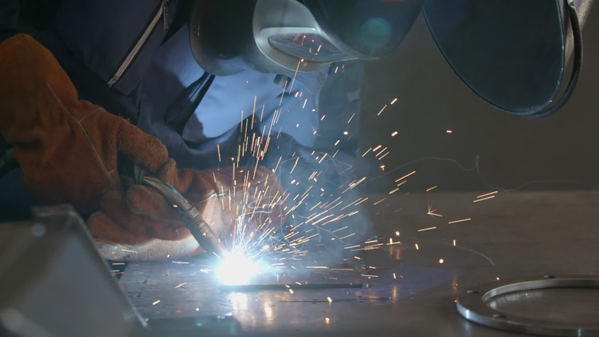 Close-up blacksmith welder in protective mask works with metal steel and iron using a welding machine, bright sparks and flashes in extreme slow motion   Shutterstock HD Video #1037172974