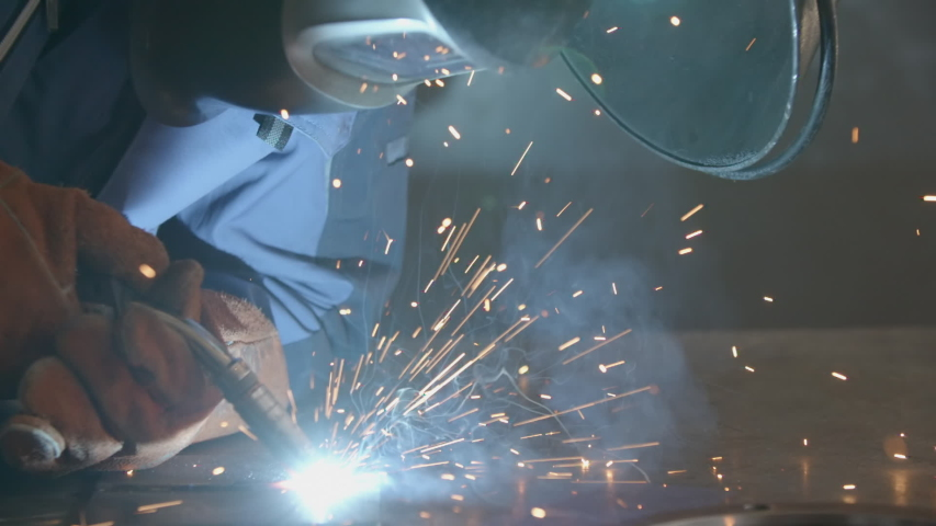 Close-up blacksmith welder in protective mask works with metal using a welding machine, bright sparks and flashes in super slow motion   Shutterstock HD Video #1037172983