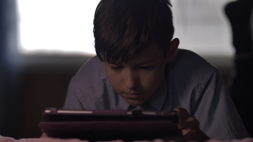 Boy lies on the bed at home and uses the tablet | Shutterstock HD Video #1037175851