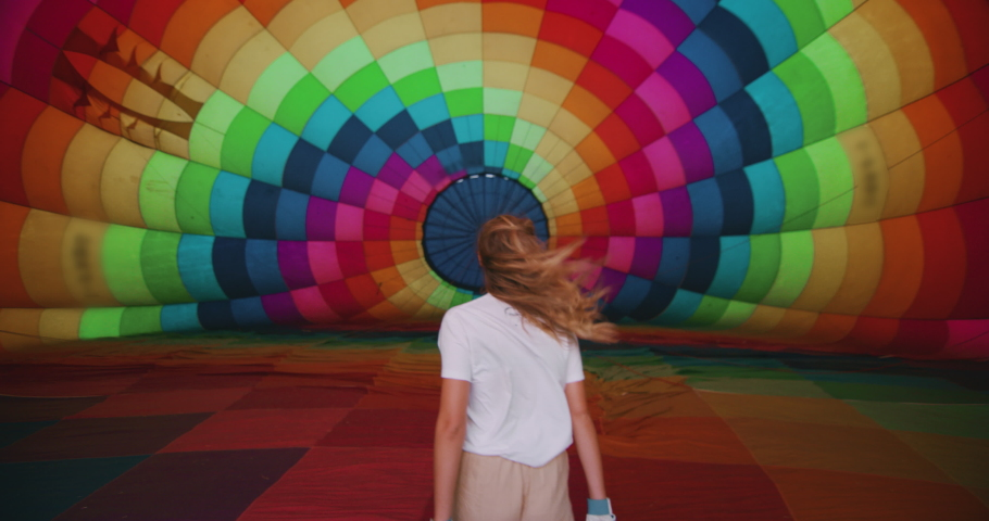 Authentic slow motion of young female pilot is entering inside of colorful hot air balloon during inflation before the flight.
