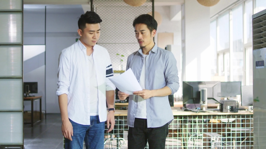 two young asian entrepreneurs discussing business while walking in office Royalty-Free Stock Footage #1037186069